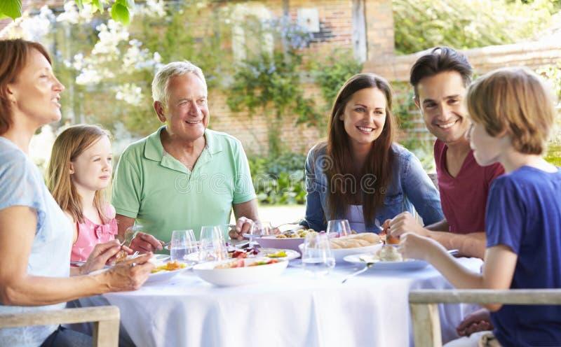 Mång- utvecklingsfamilj som tillsammans tycker om utomhus- mål royaltyfri bild