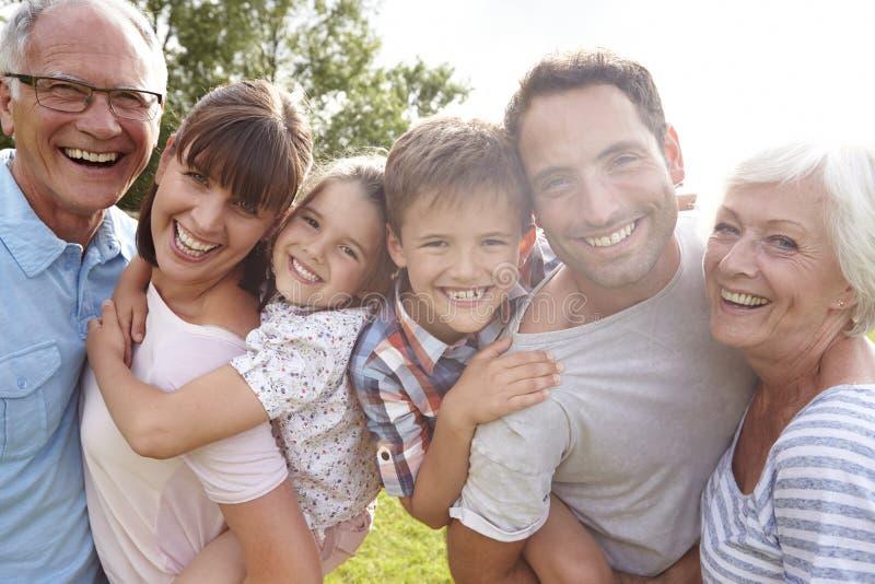 Mång- utvecklingsfamilj som utomhus ger barn ridturer på axlarna royaltyfria foton