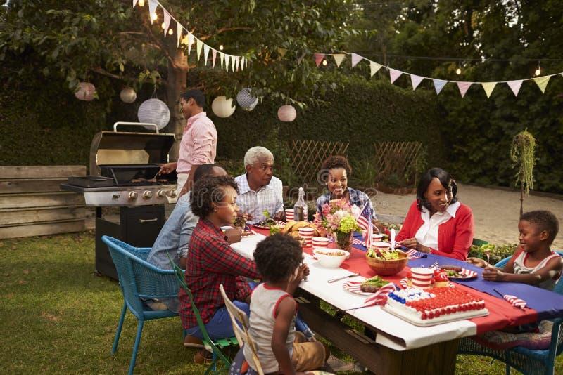 Mång- utvecklingssvartfamilj som har 4th en Juli grillfest royaltyfria foton