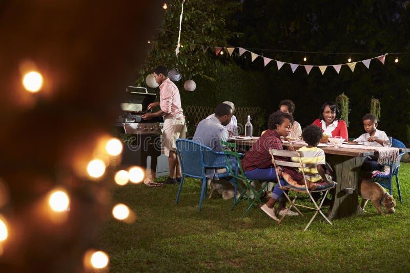 Mång- utvecklingssvartfamilj som tycker om en grillfestmatställe royaltyfria bilder