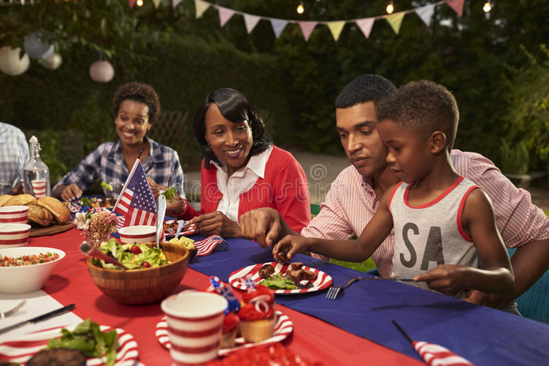 Mång- utvecklingssvartfamiljemedlemmar på 4th en Juli grillfest royaltyfria bilder