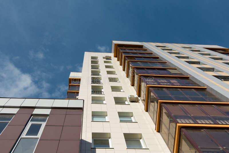 Mång--våning bostads- hyreshusar över blå himmel fotografering för bildbyråer