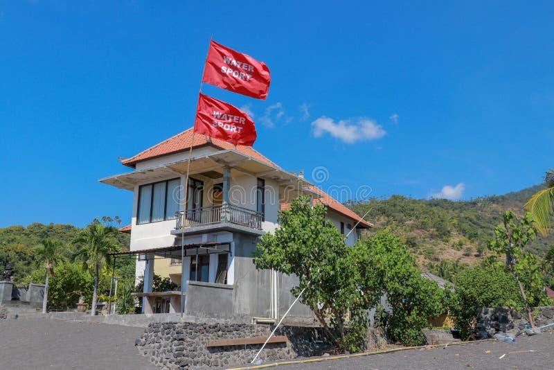 Mång--våning strandhus med vulkanisk sand Röd flagga med inskriften som fladdrar i vinden Berg i bakgrunden och royaltyfri bild