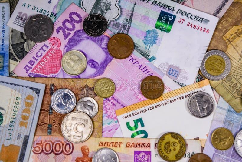 Mång- valutabakgrund Euro amerikanska dollar, ukrainska hryvnias, egyptiska pund, ryssrubel, olika mynt royaltyfri fotografi