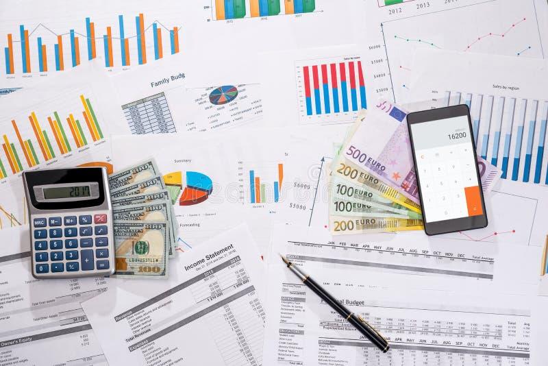 Många affärsgraf med mobil-, dollar- och euroräkningar, räknemaskin arkivfoto