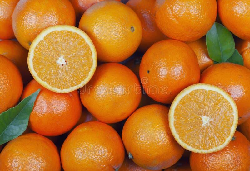 Många apelsiner med något snitt i halva arkivfoto