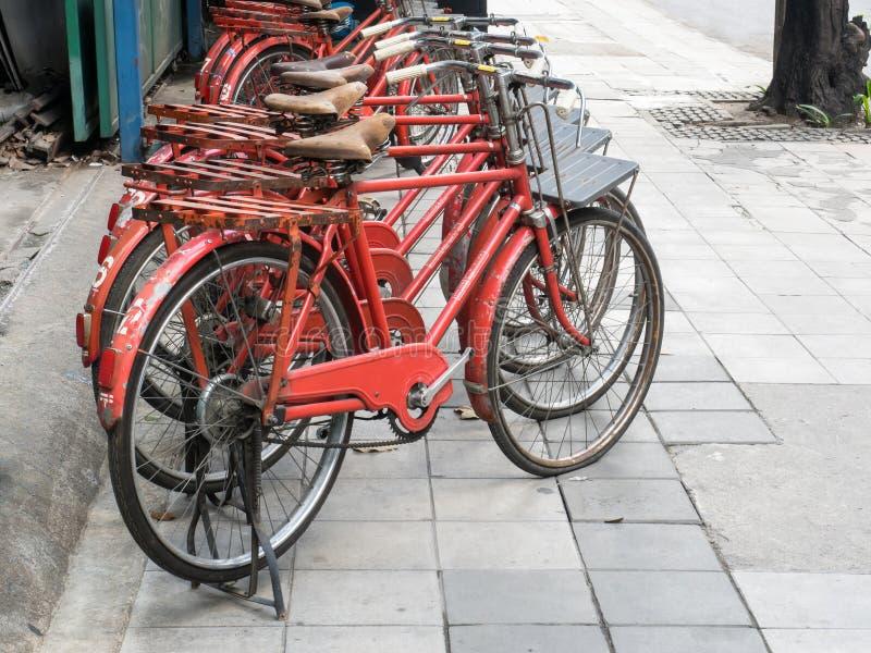 Många av rött klassiskt parkera för cyklar arkivbilder