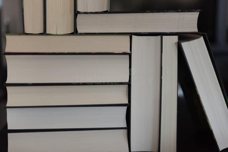 Många böcker som travas upp arkivfoto