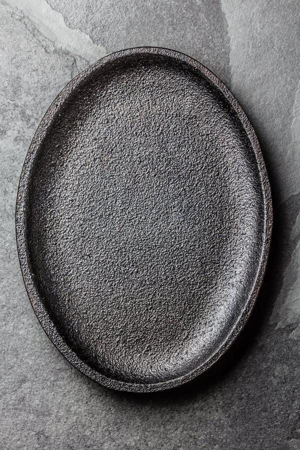 många bakgrundsklimpmat meat mycket Svart platta för tomt gjutjärn arkivbild