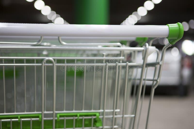 Många belägger med metall shoppingvagnar på en parkeringsplats nära supermarket utomhus ben för bakgrundspåsebegrepp som shoppar  arkivbilder