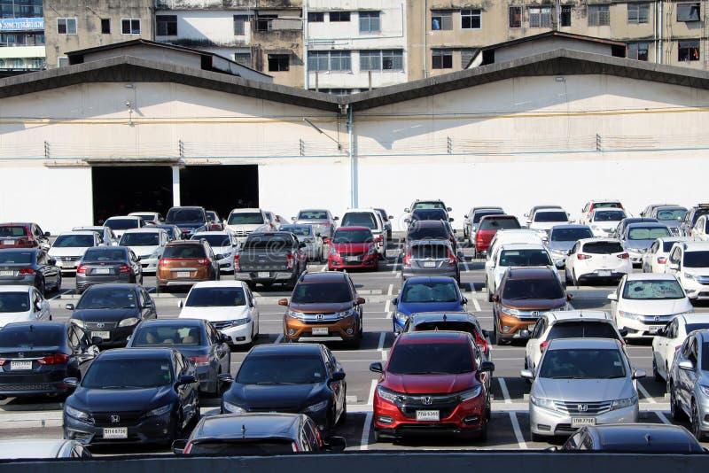 Många bilar parkeras på den utomhus- parkeringsplatsen med garagebyggnad och mer högväxt byggnad royaltyfri foto