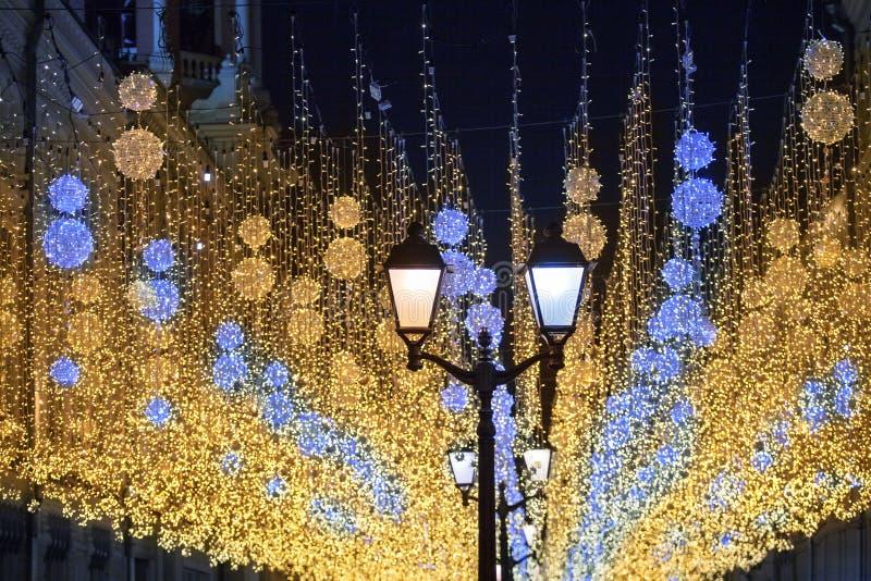 Många blåa ljusa brinnande ljus och gula lyktor som hänger på den svarta closeupen för bakgrund för natthimmel royaltyfria bilder