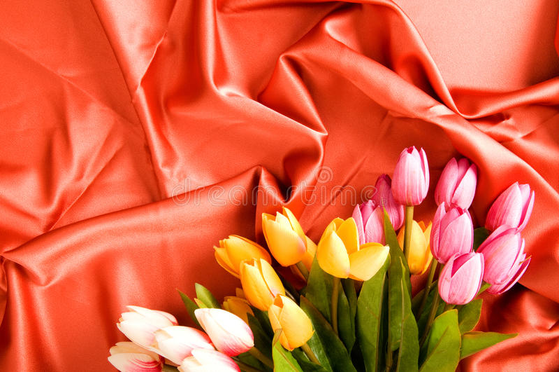 Många blommor på den röda satängen arkivfoto