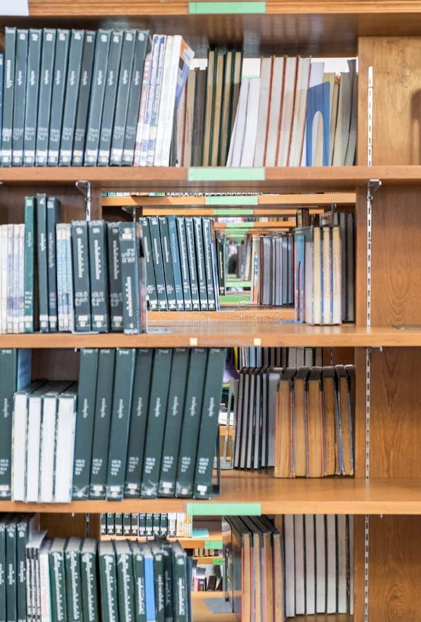 Många bokslag som staplas på trähylla arkivbild