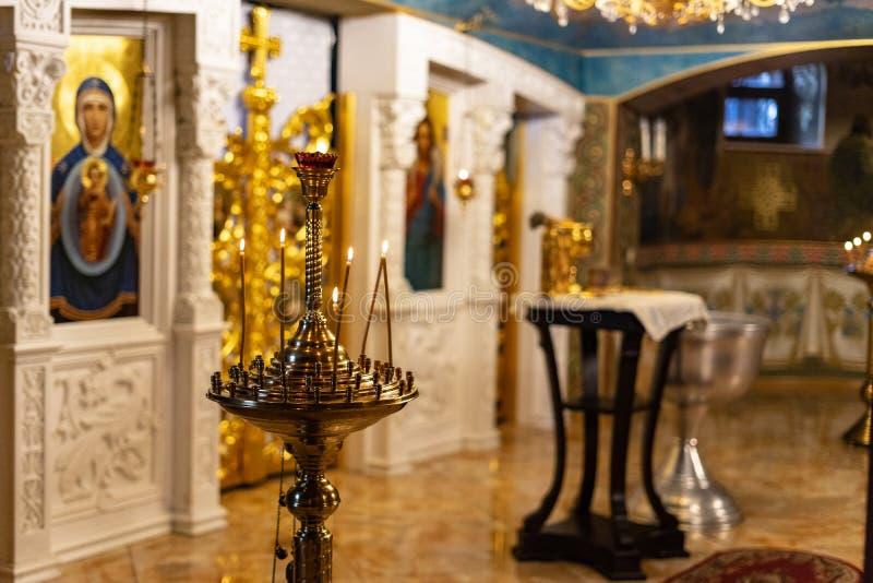 Många brinnande vaxstearinljus i den ortodoxa kyrkan arkivfoto