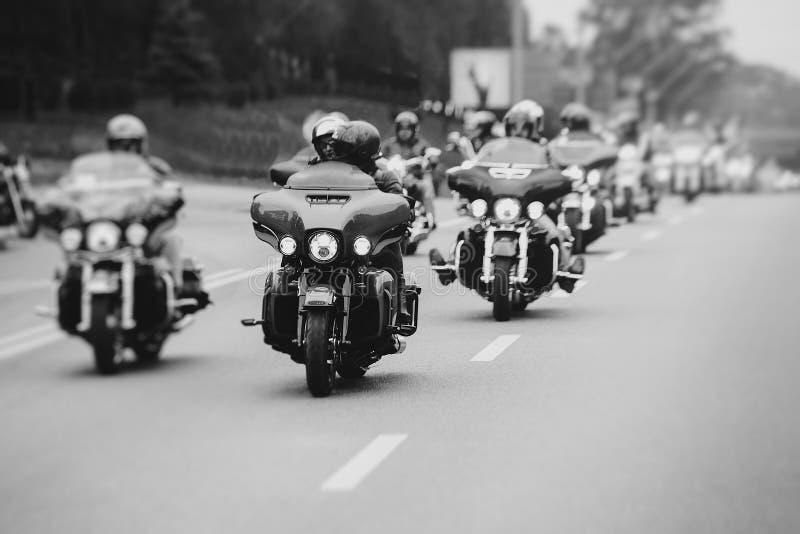 Många cyklister rider motorcyklar på huvudvägen i staden, ett svartvitt foto royaltyfri bild