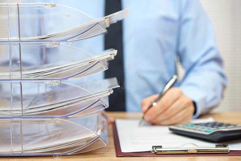 Många dokument som är ordnade i en mapp, bordlägger, skrivbordsarbete och accoun arkivbilder