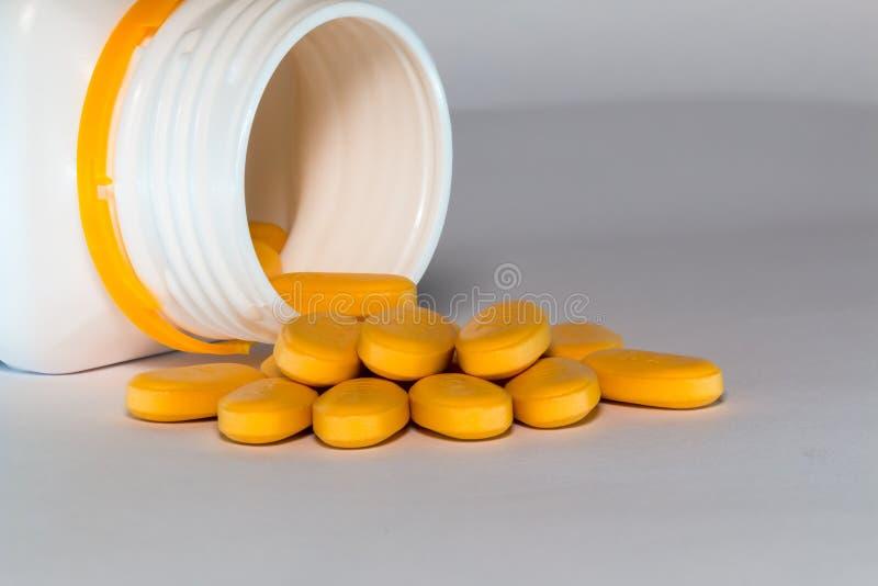 Många dos av orange medicinminnestavlor som ut spiller arkivbild