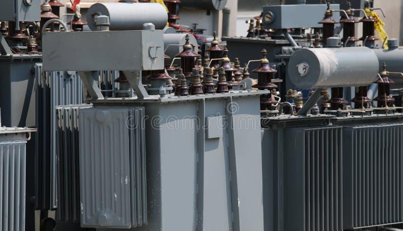 många elektriska transformatorer som omformar spänningen från höjdpunkt arkivfoto