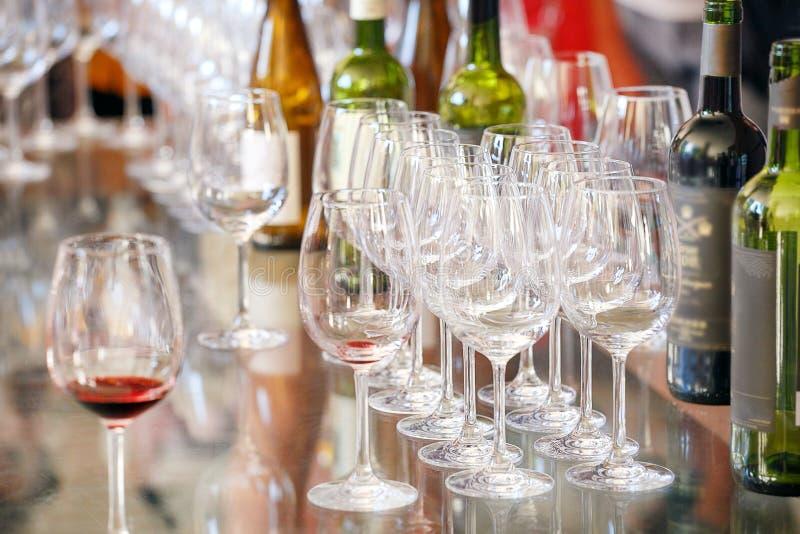 Många exponeringsglas och flaskor av olikt vin på en tabell royaltyfria foton