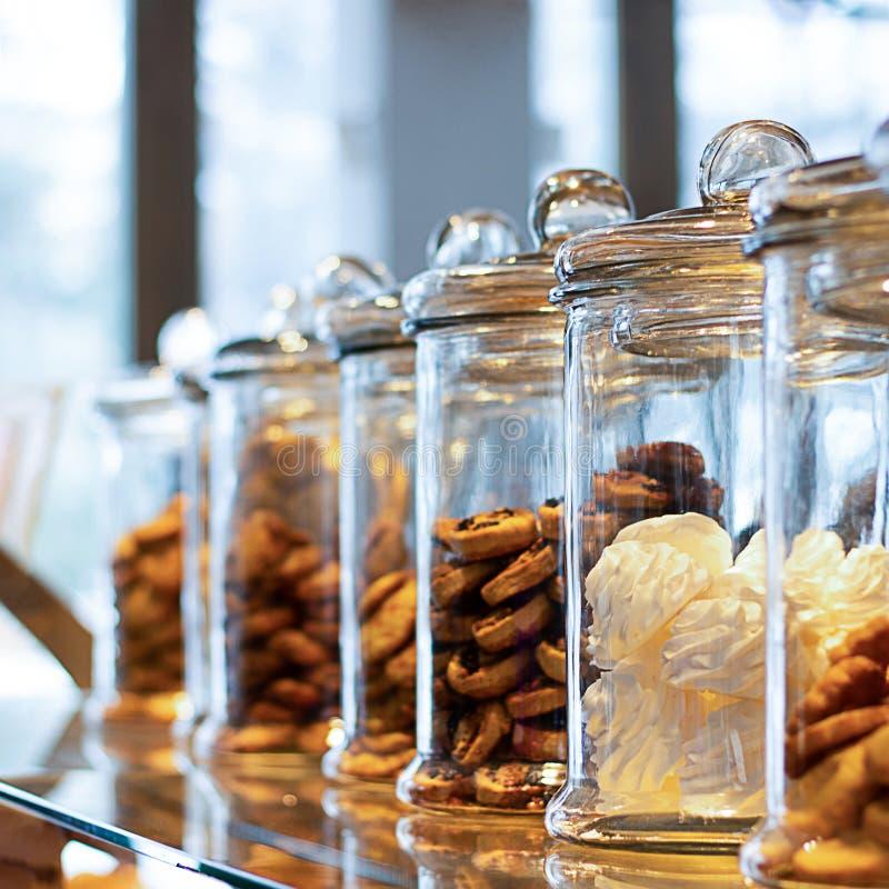 Många exponeringsglaskrus med lock som fylls med kakor och sötsaker, på defocused bakgrund med reflexion Krus innehåller träsk-ma royaltyfria foton