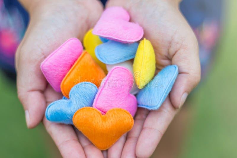 Många färgrik hjärta i kvinnahänder för att ge till hers vänner royaltyfria bilder