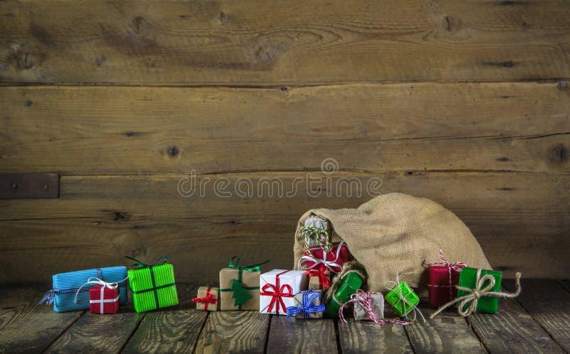 Många färgrika julgåvor på trägammal bakgrund arkivfoton
