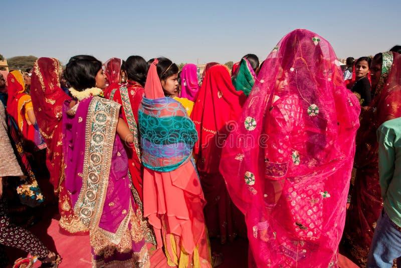Många färgrika kvinnor i sarianseende i folkmassa royaltyfria bilder