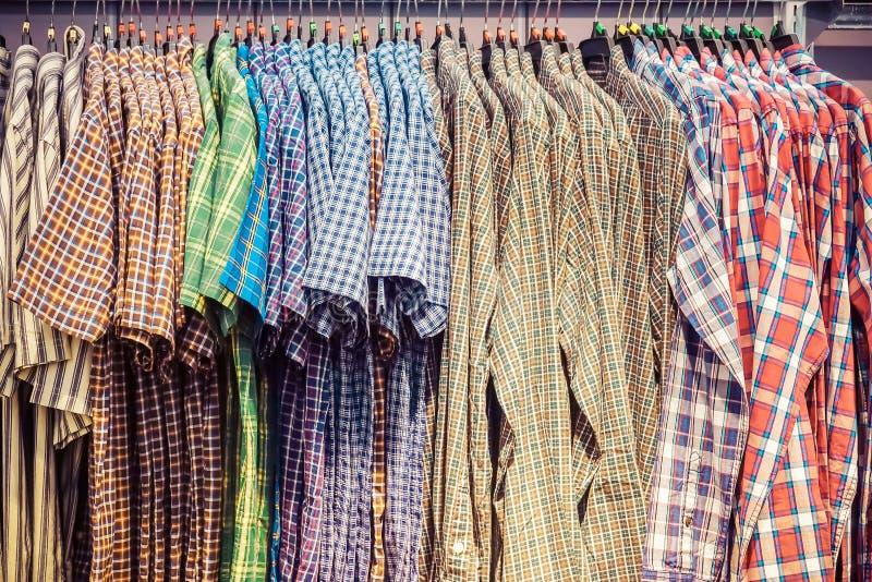 Många färgrika rutiga formella manskjortor som hänger på en kugge, rad av mäns dräkter som hänger i garderob, begrepp av köpet oc arkivbild