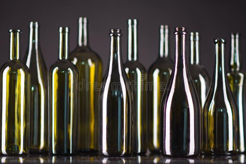 Många flaskor på en grön bakgrund arkivfoto