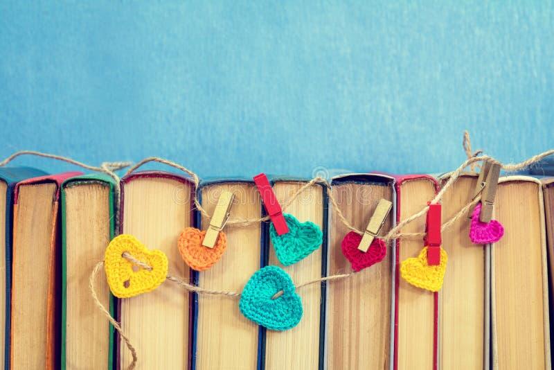 Många flerfärgade virkninghjärtor på böcker royaltyfri foto