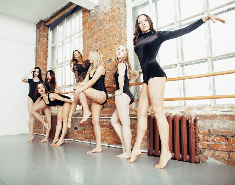 Många flickor som utbildar i studiobalett, den långa kvinnan, lägger benen på ryggen sexigt stödja som bär den sexuella svarta bo arkivbilder