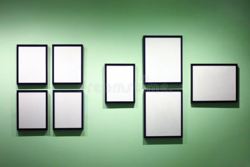 Många fotoramar som hänger på den gröna väggen, utställningutrymme fotografering för bildbyråer