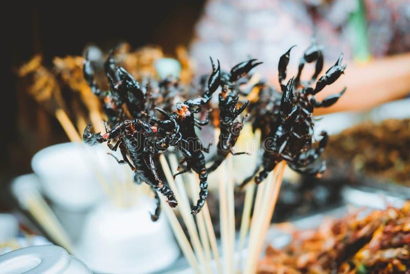 Många friterade skorpion på skevrar på Yaowarat Road vid Chinatown i Bangkok, Thailand Gatumat i berömd arkivfoton
