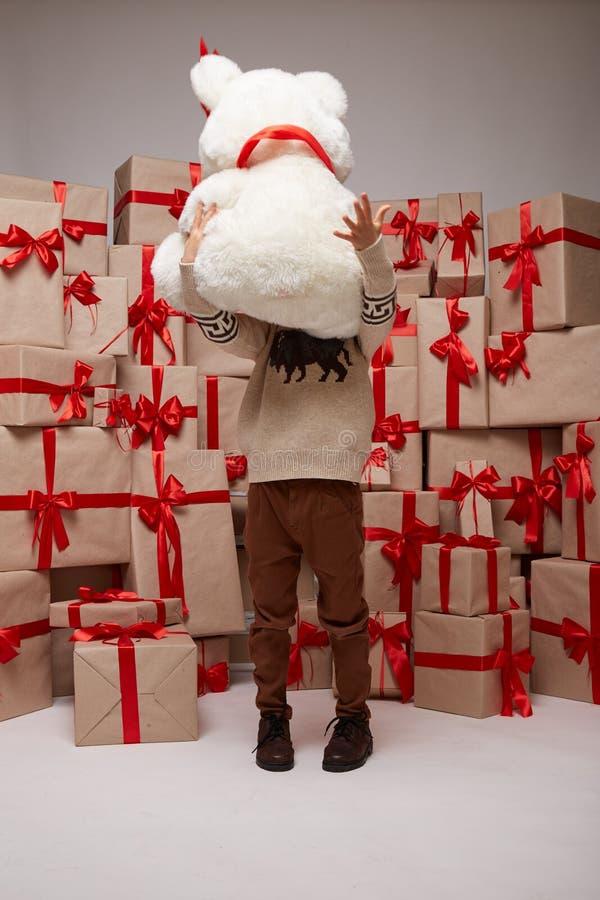 Många gåvor, askar med gåvor som täckas med det röda satäng- och silkebandet med den stora pilbågen, glad jul och ett lyckligt ny arkivfoto