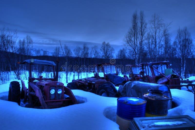 Många gamla vibrerande red ut traktorer i snöig delgård royaltyfria bilder