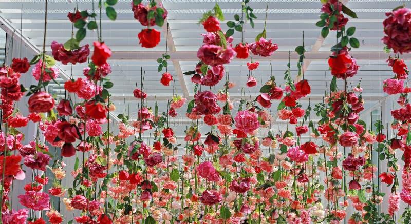 Många garnering för bröllopceremoni med den konstgjorda blomman som hänger från tak Härliga uppochnervända blommor royaltyfri fotografi