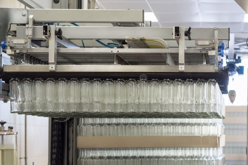 Många glasflaskor som hänger i en pneumatisk gripare Avlastning av glasflaskor från paletter royaltyfria bilder