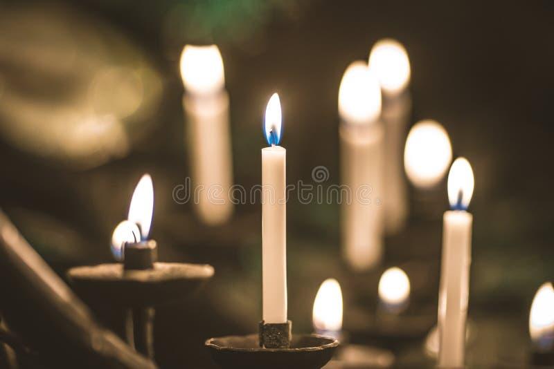 Många gula stearinljus för brinnande kyrkligt vax i stort på en special ställning arkivbild