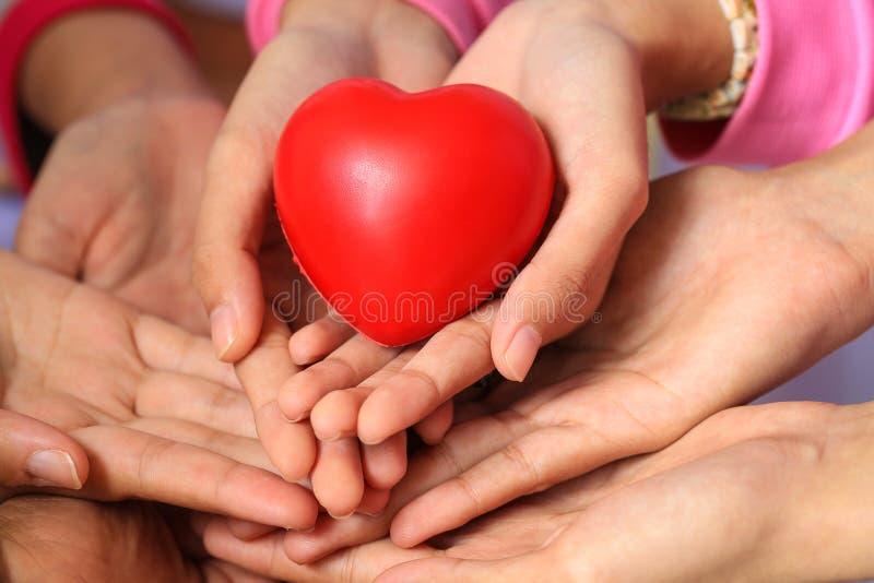 Många händer och en röd hjärta royaltyfria bilder