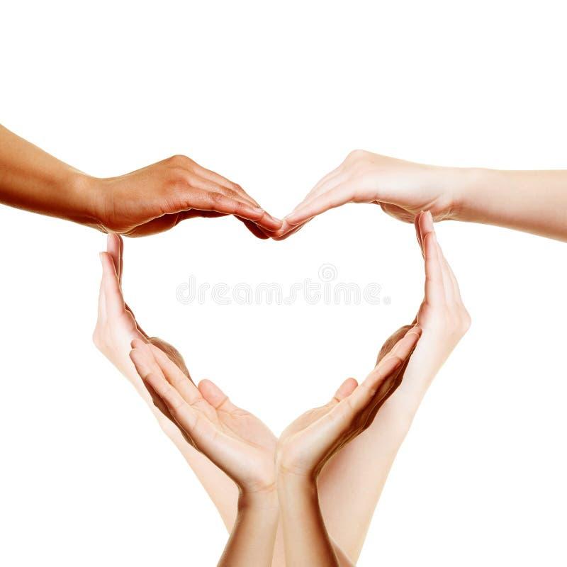 Många händer som bildar en förälskelsehjärta arkivfoto