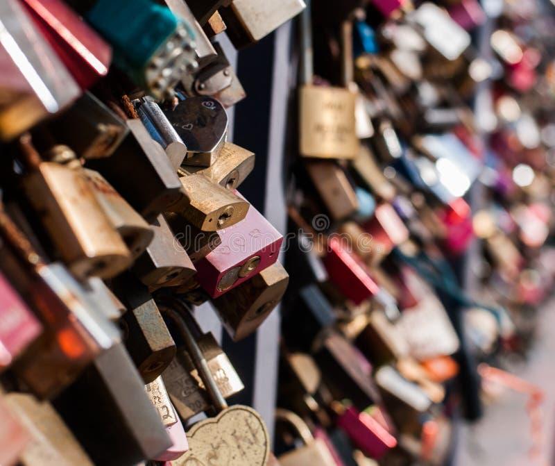 Många hänglås på staketet som symboliserar förälskelse arkivfoto