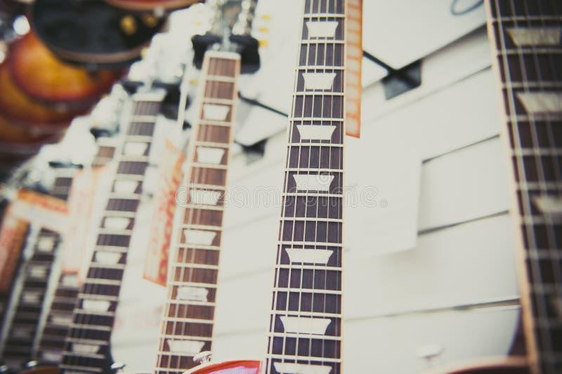 Många halsar för elektrisk gitarr som arrangera i rak linje i lager arkivbild