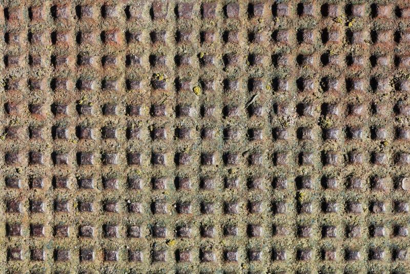 Många handgjorda fyrkantiga hål i det rostiga tappningarket för järn royaltyfria foton