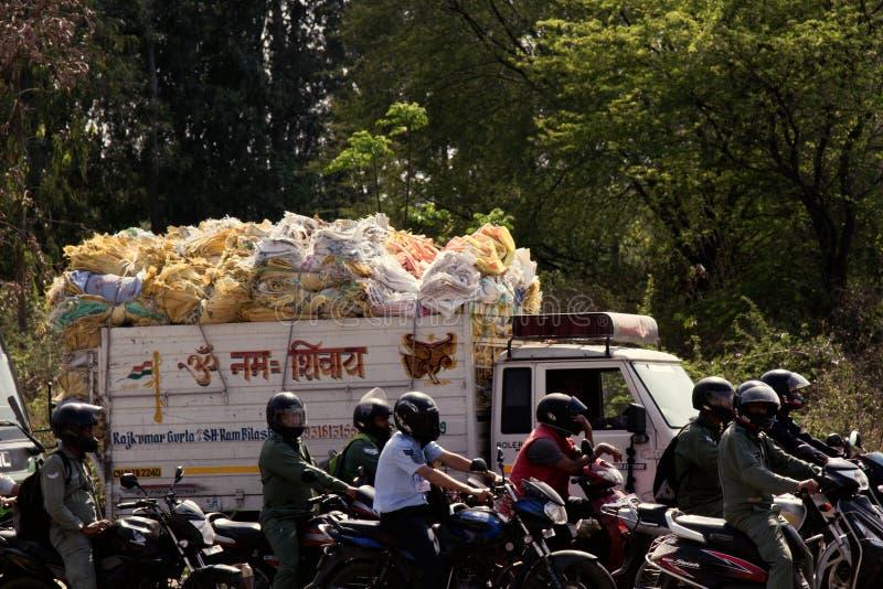 Många indiska motorcyklister och lastbil med högen av färgrika påsar royaltyfri foto