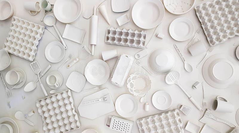 Många köksgerådkoppar, plattor, rånar, gafflar, skyfflar, rivjärn, kavlen, skeden, konservöppnare målat vitt på vit arkivfoto