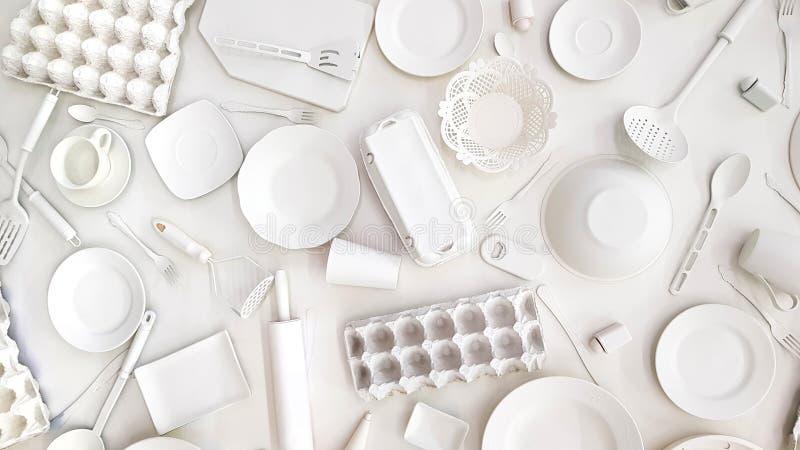 Många köksgerådkoppar, plattor, rånar, gafflar, skyfflar, rivjärn, kavlen, skeden, konservöppnare målat vitt på vit royaltyfria foton