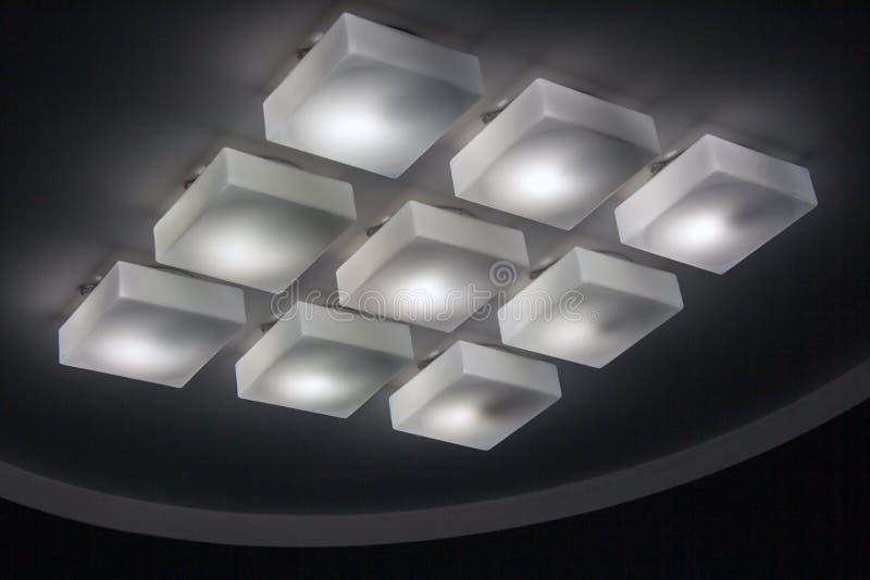 Många kallt lampor för tända i kontorsbyggnadlobbyen arkivbild