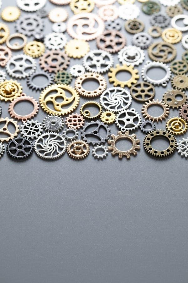 Många kugghjul - små delar av klockan på en grå bakgrund arkivbild