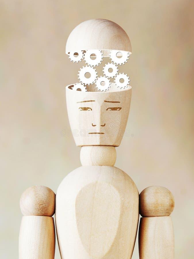 Många kugghjul som arbetar in i det mänskliga huvudet arkivfoto